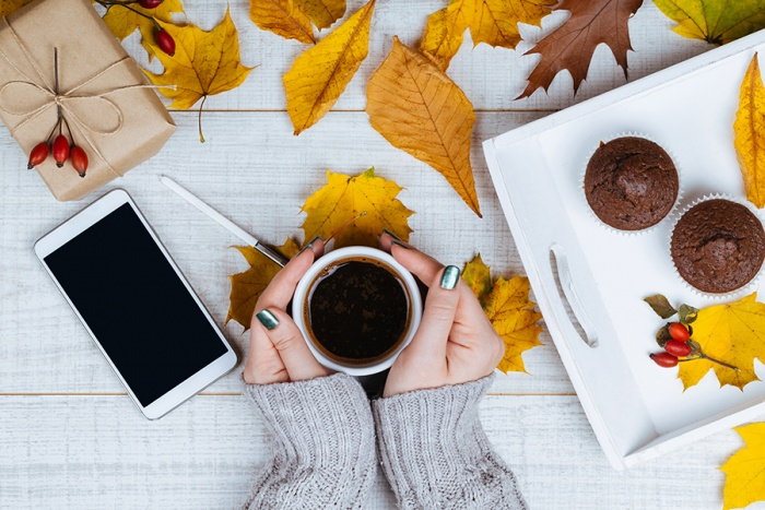 hands holding coffee with mobile phone and muffins